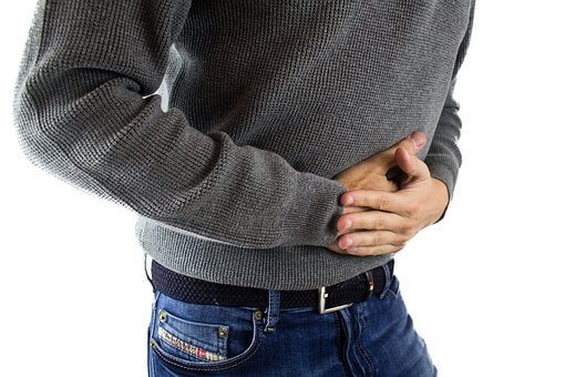 Man holding his stomach due to stomach ache