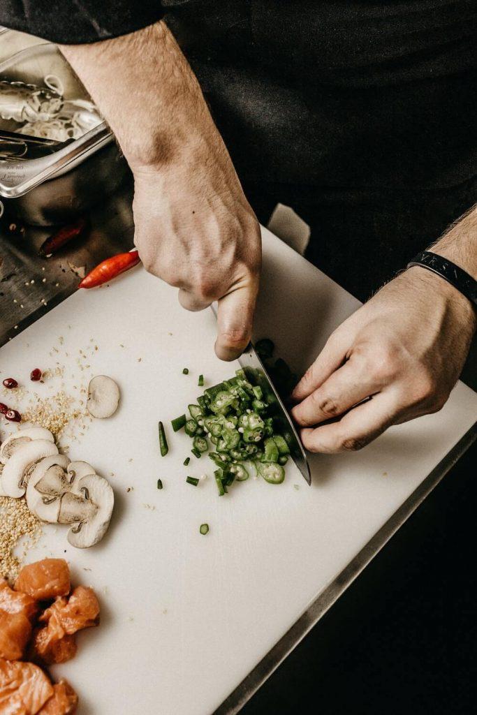 Chopping pepper on a white chop board