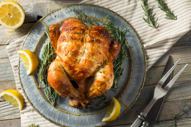 Nice looking whole chicken on a blue plate with slices of lemon and rosemary