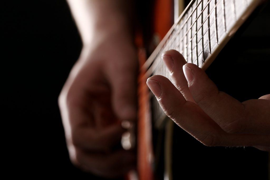 man playing low action acoustic guitars